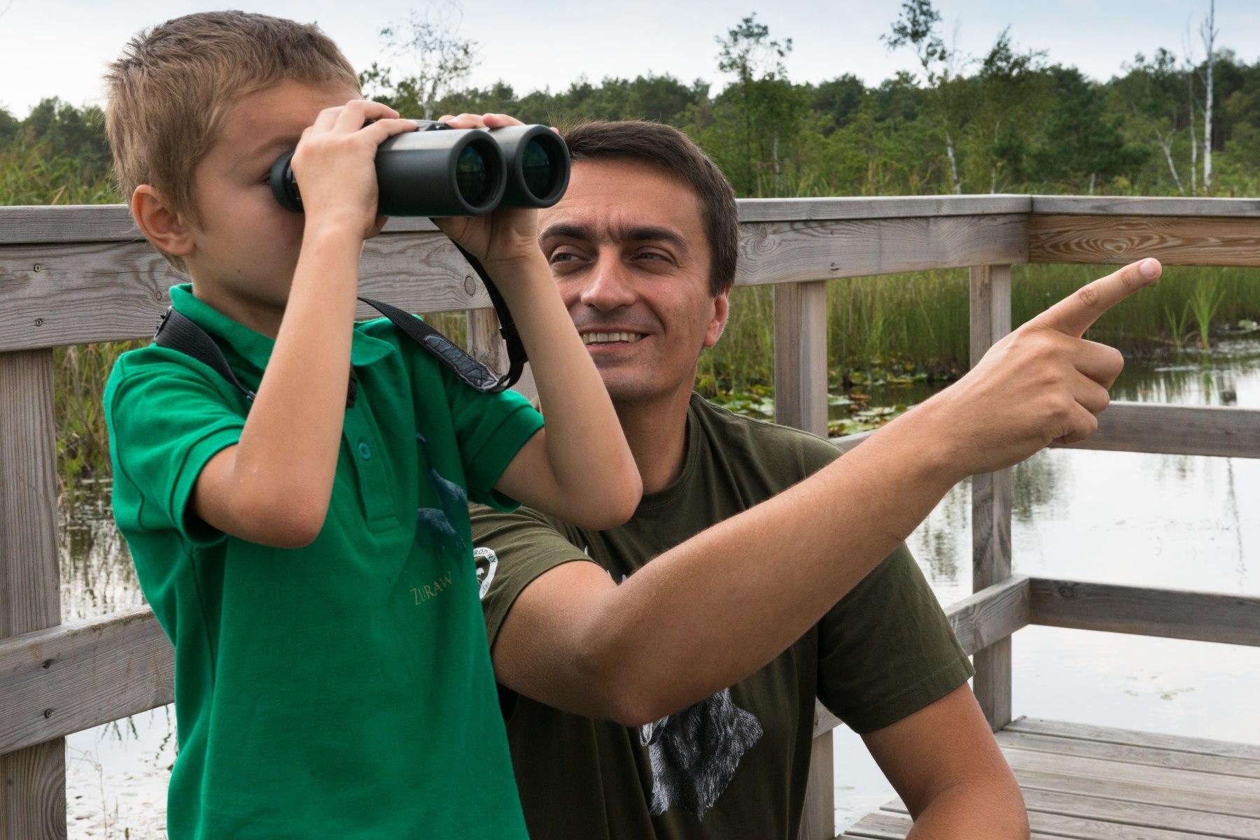Mężczyzna patrzy się na chłopca, który obserwuje coś przez lornetkę