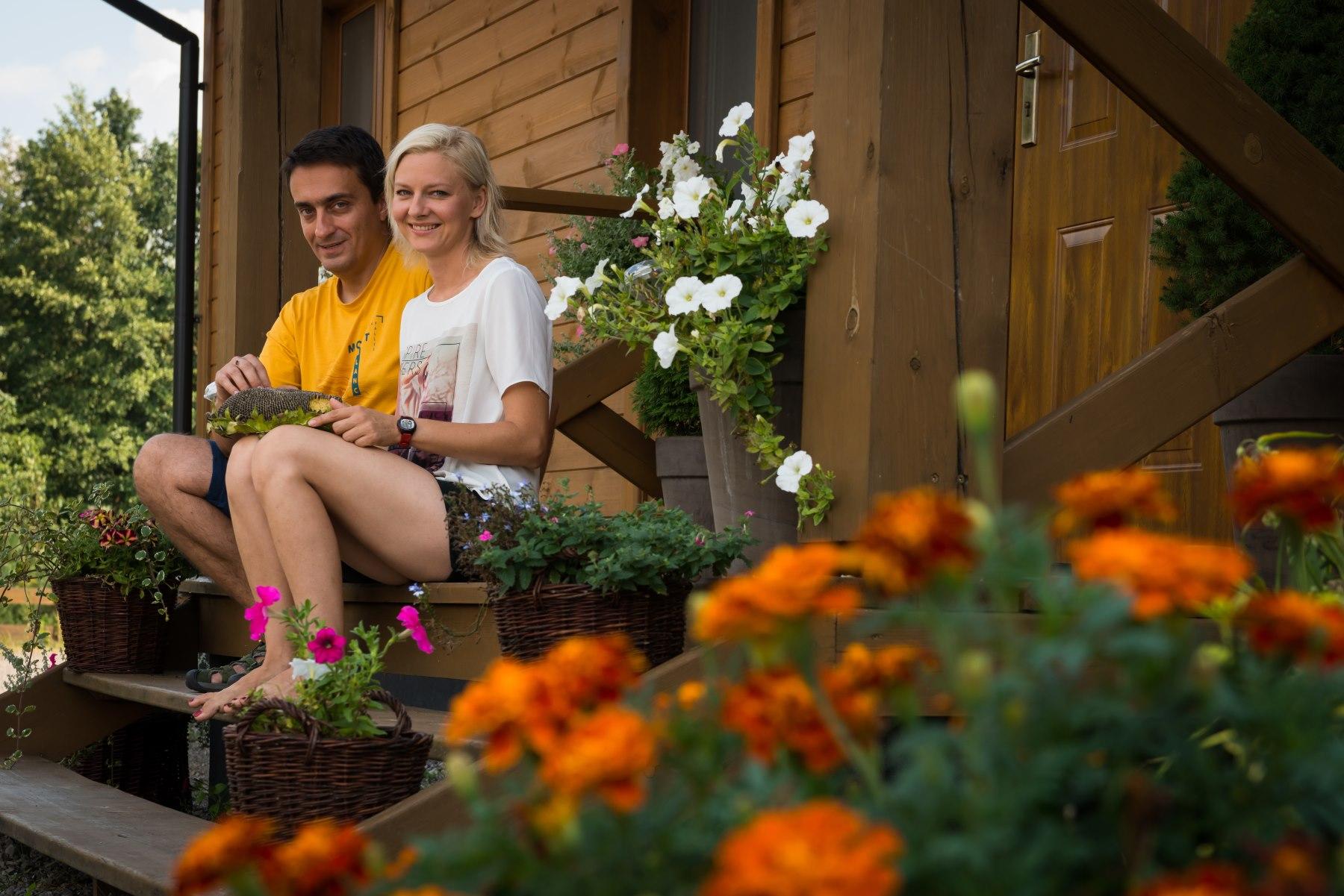 Para siedząca na drewnianych schodach- gospodarze Agroturystyki Polesie