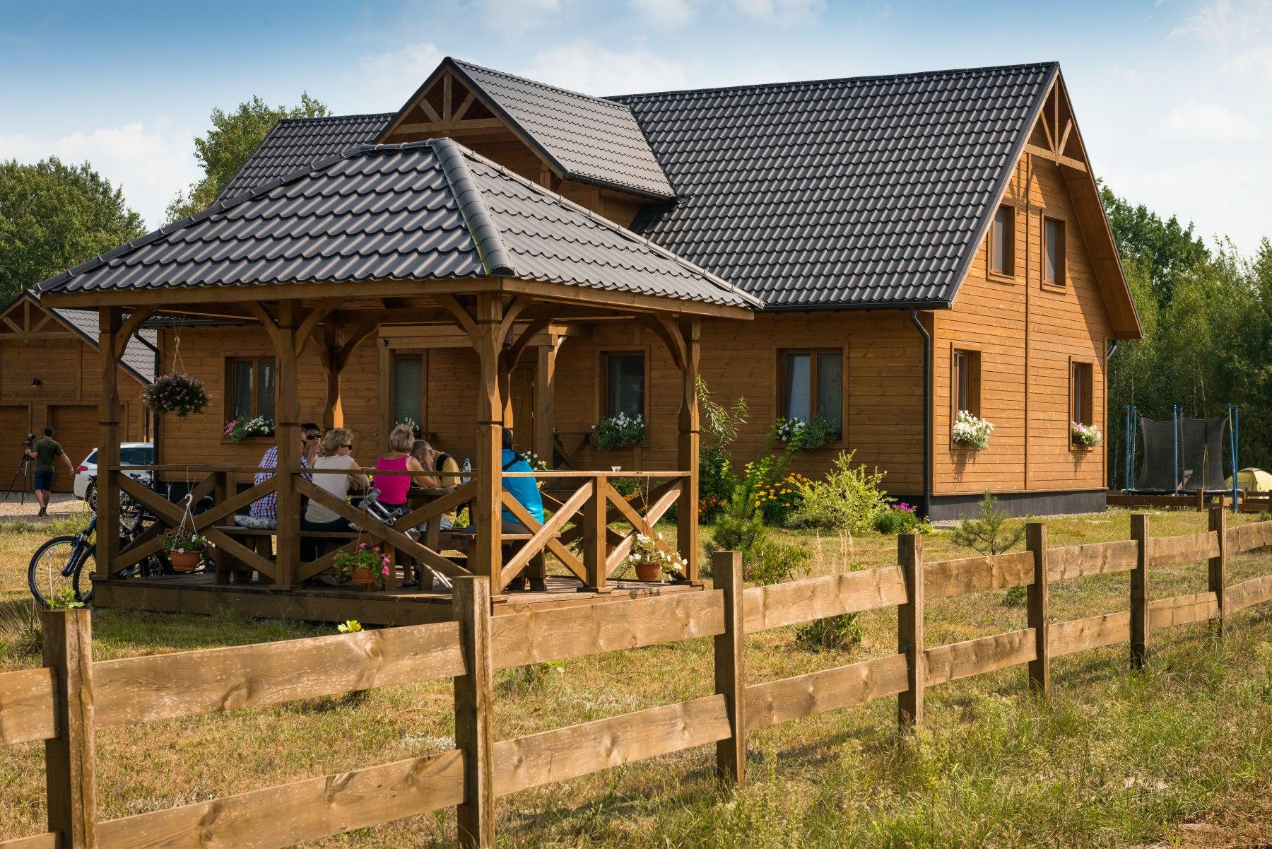 Drewniany dom otoczony płotem