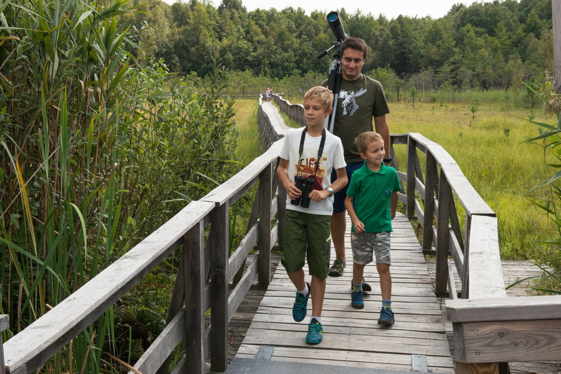 Mężczyzna i dwóch chłopców idą po drewnianym moście