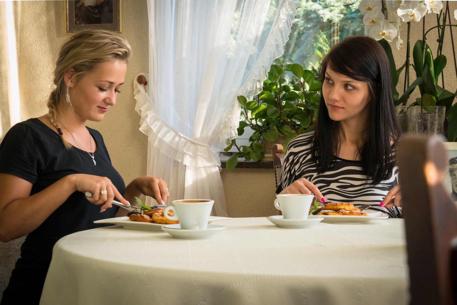 Dwie kobiety jedzą przy stole regionalne dania