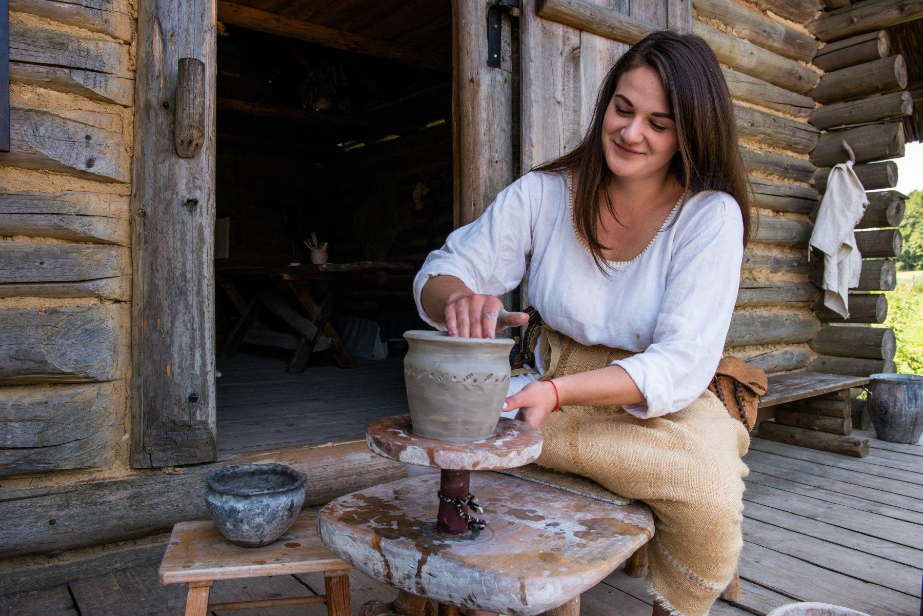Dziewczyna wyrabia gliniane naczynie na kole garncarskim