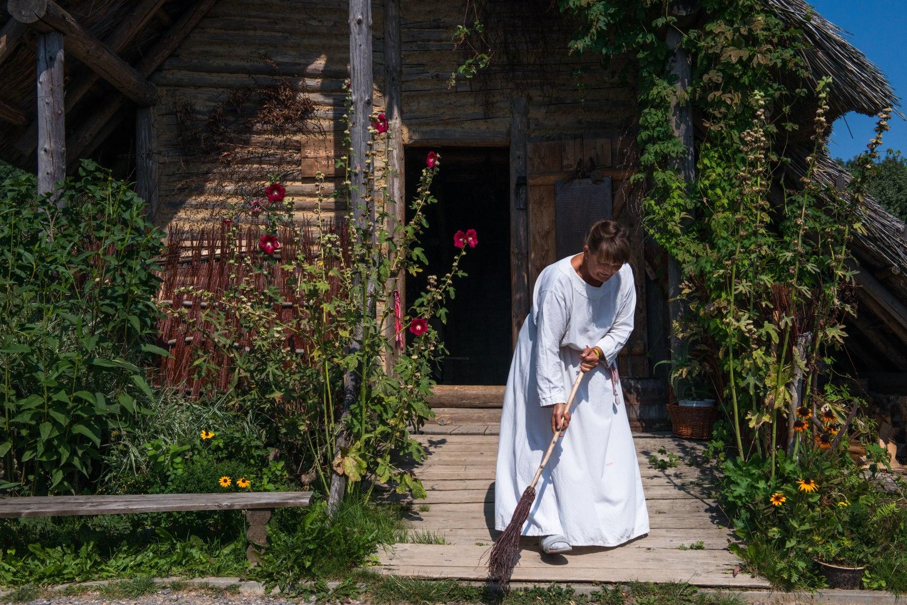 Kobieta zamiata przed drewnianym domem