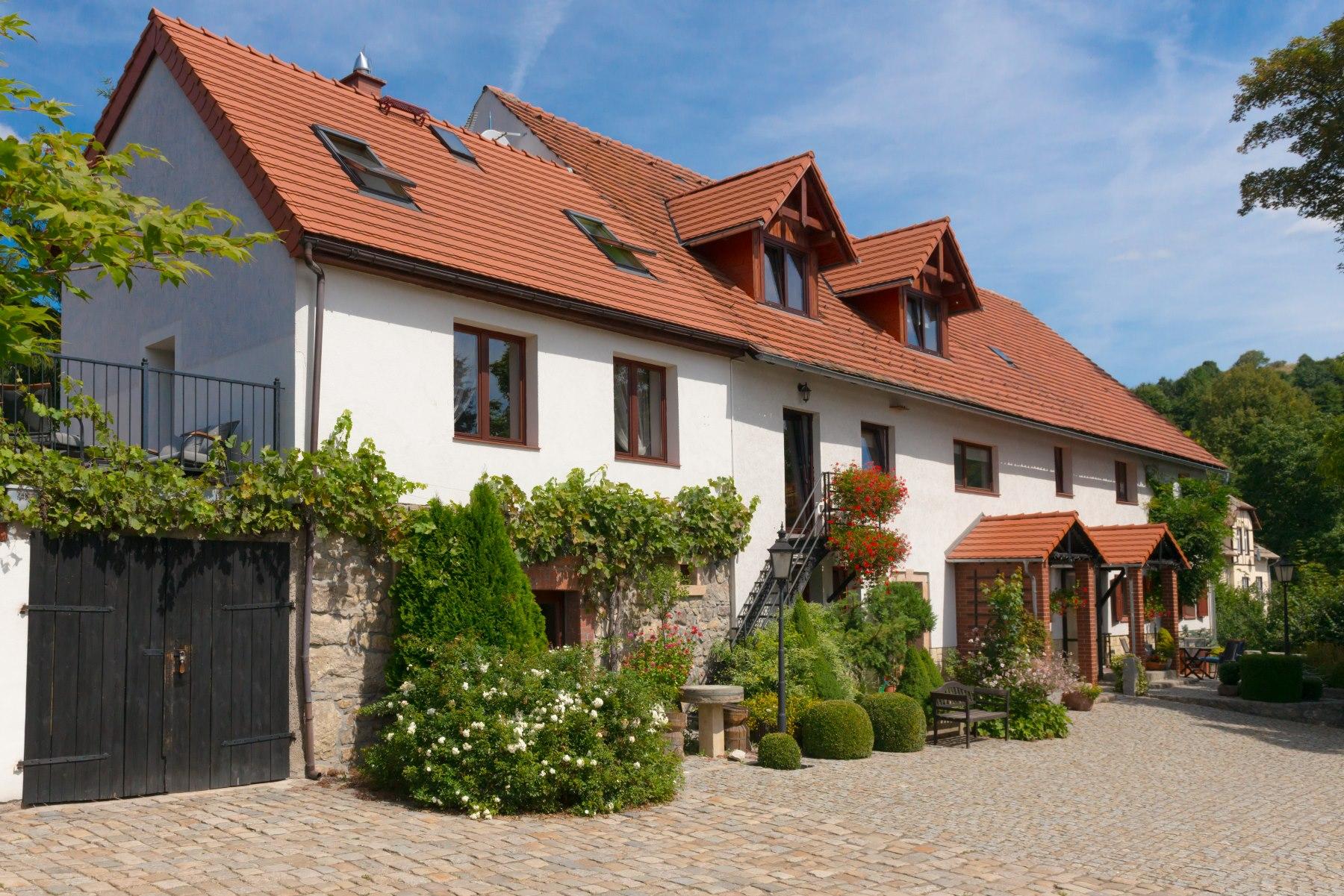 Biały dom z czerwonym dachem, porośnięty zielenią - agroturystyka Pod Srebrną Górą