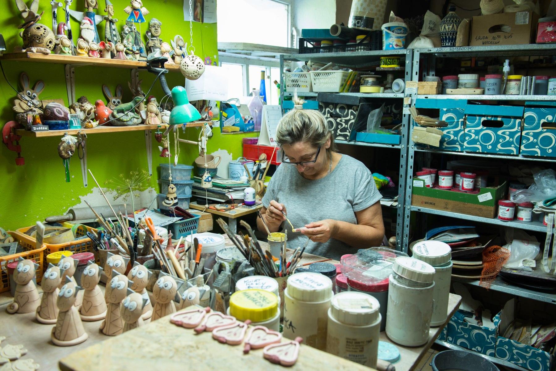 Kobieta w okularach maluje wyroby ceramiczne