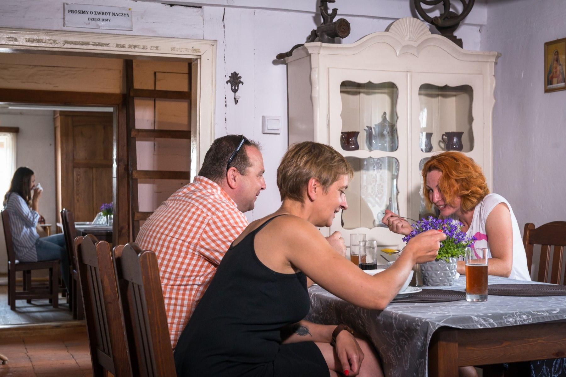 Mężczyzna i dwie kobiety jedzą przy stole