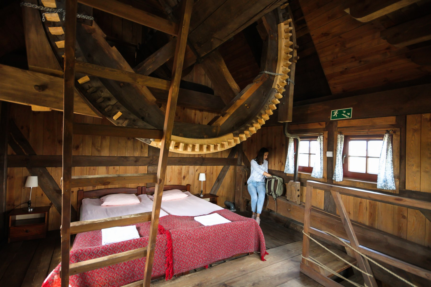Duże łóżko w drewnianym wnętrzu starego młyna